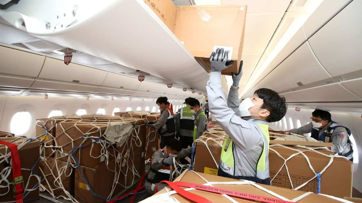 Boxes being loaded in overhead bins and on floor of passenger plane with no seats.