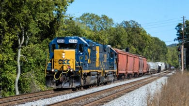 A photograph of a CSX train traveling by a forest.
