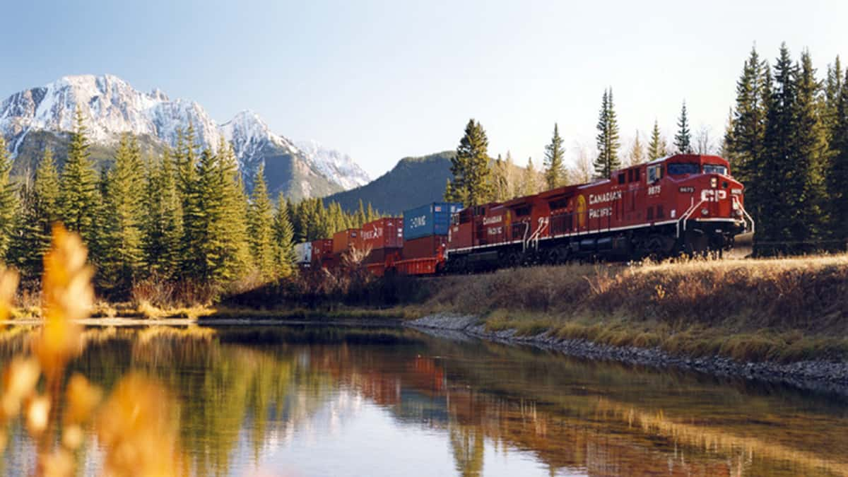 A photograph of a Canadian Pacific train traveling by a lake.