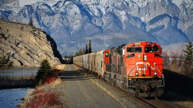 A photograph of a CN train traveling away from a high mountain range.
