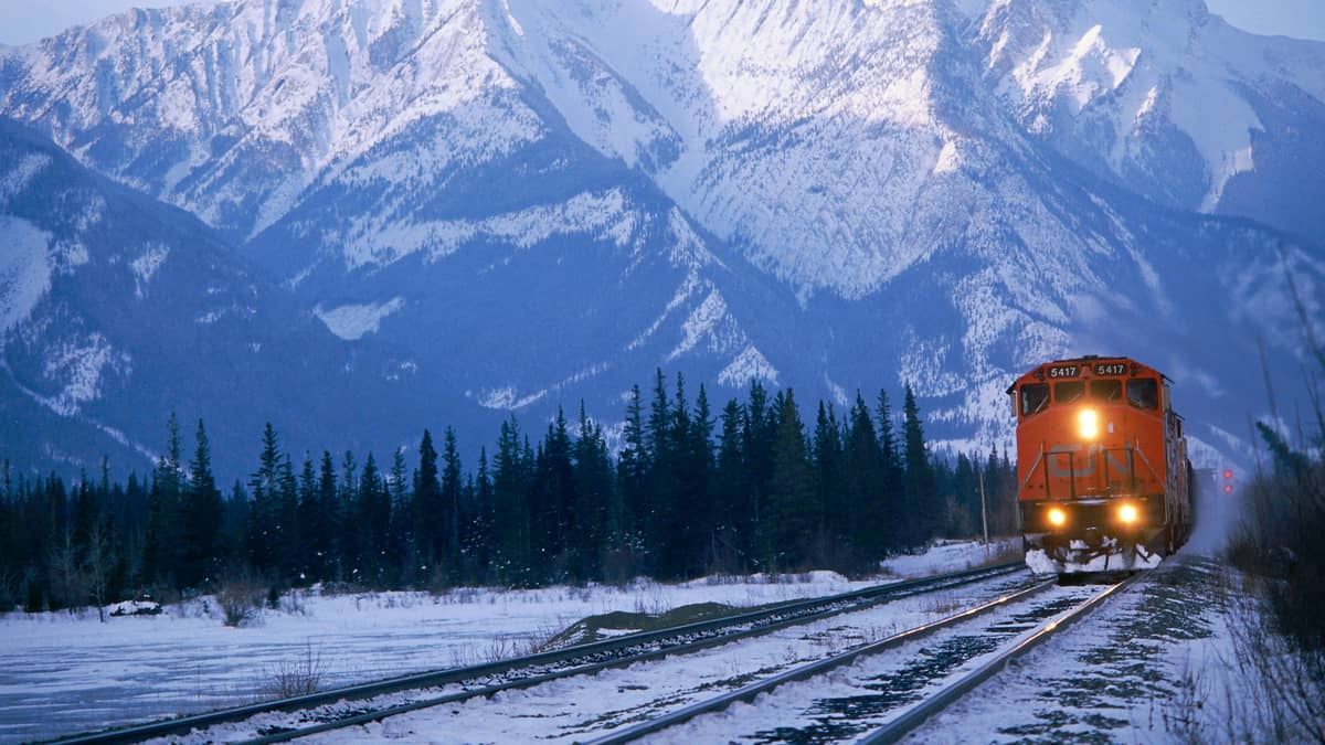 A photograph of a CN train heading away from a snow-capped mountain.