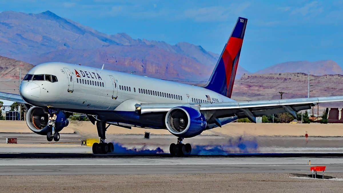 A white Delta plane with blue tail lands at sunny Las Vegas airport.