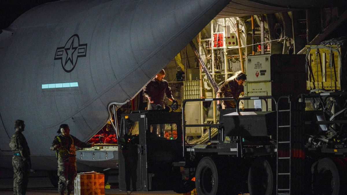 U.S. military personnel unloading equipment from back of a