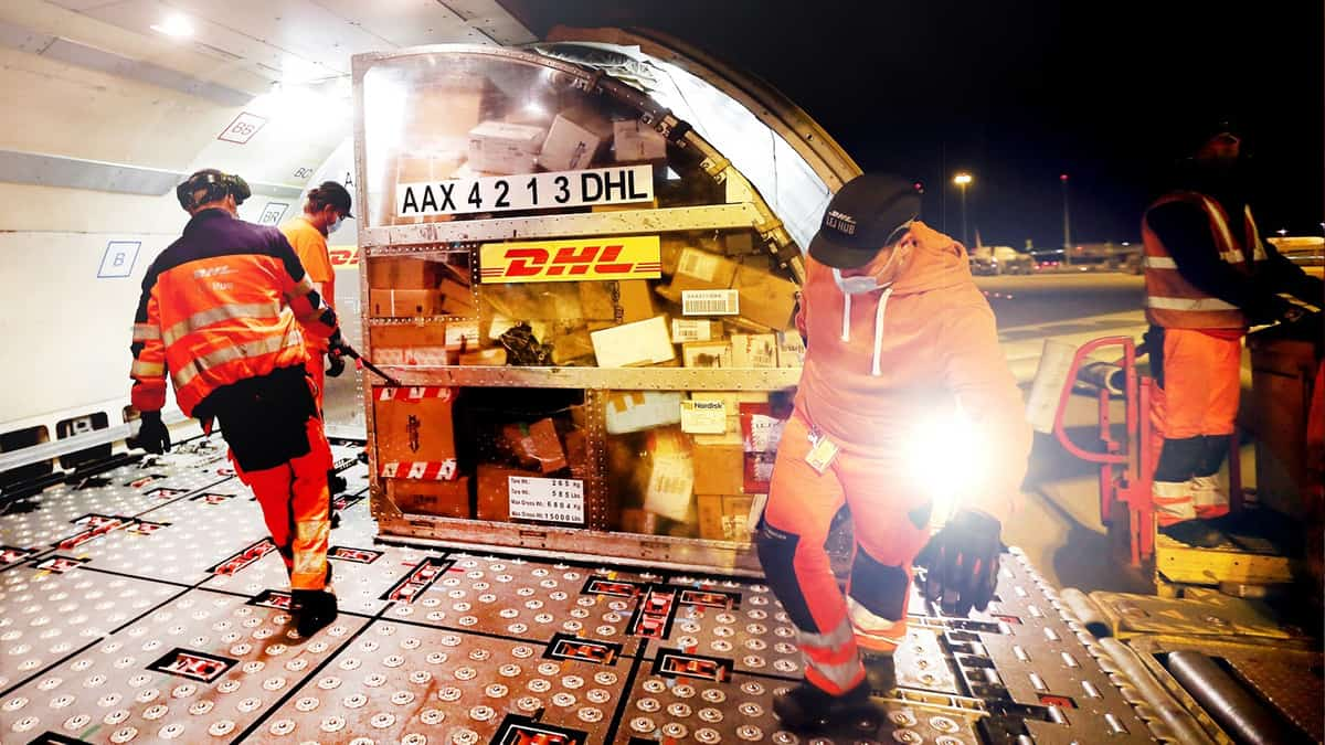Workers in yellow vests load container in illuminated cargo bay of airplane at night.