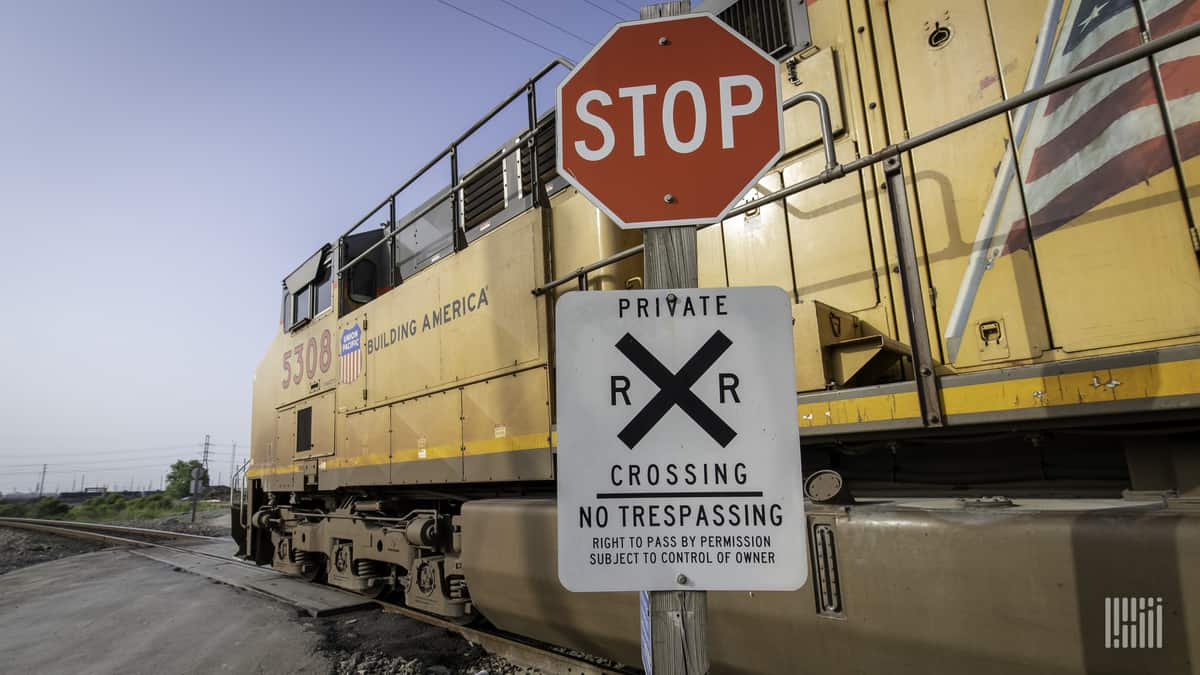 A photograph of a Union Pacific train passing by a rail crossing.