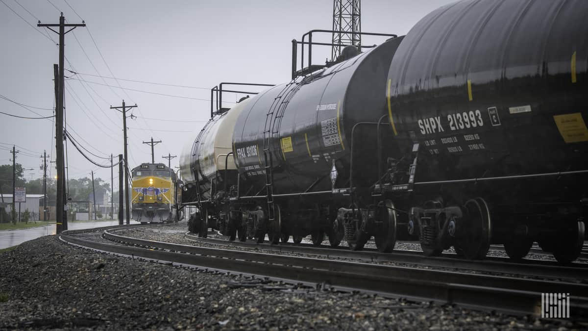 A photograph of a train with tank cars passing by a Union Pacific train.