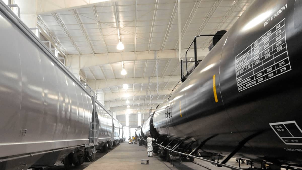 A photograph of tank cars parked inside a garage.