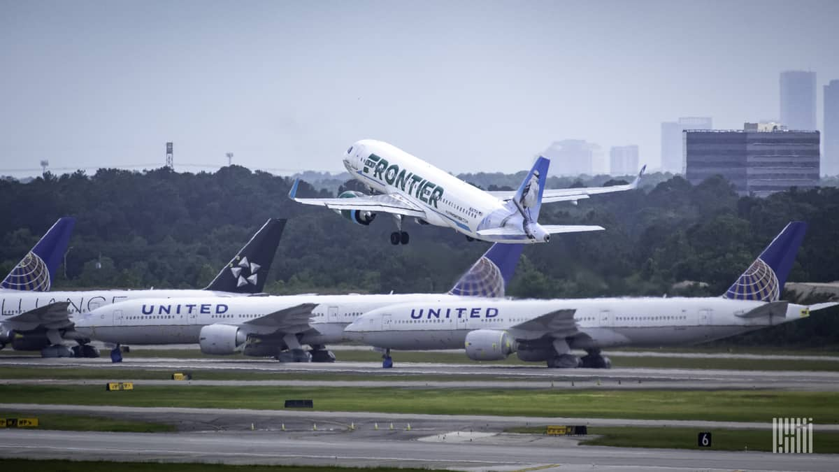 A white jet takes off with other planes sitting in the foreground and buildings from downtown Houston in the background.