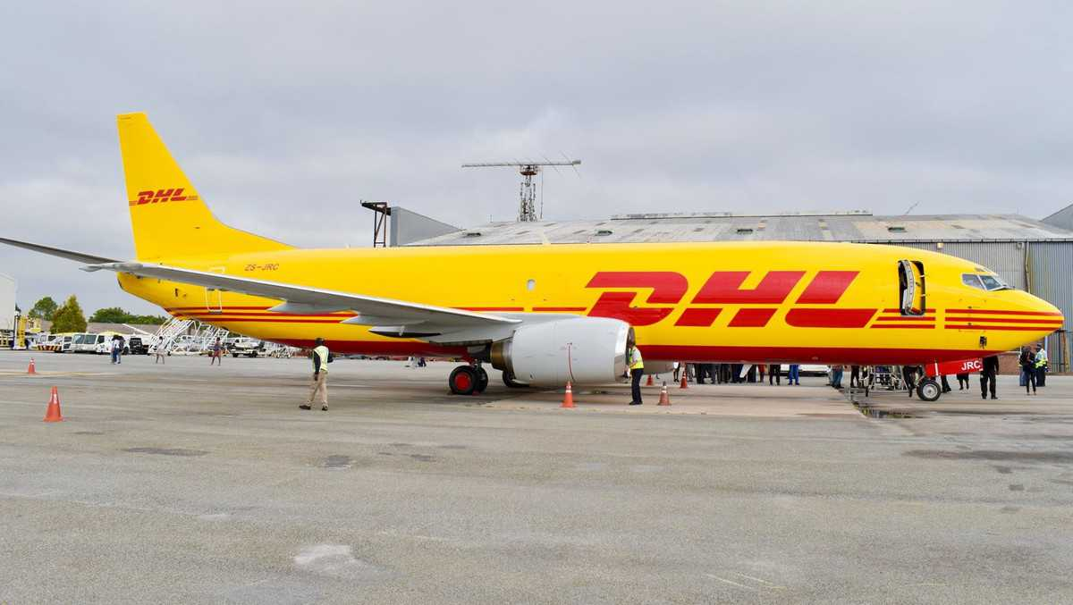 Mustard-yellow DHL freighter jet sitting at airport.