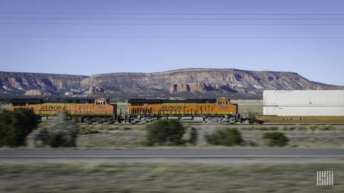 A photograph of a BNSF train traveling by a mountain range.
