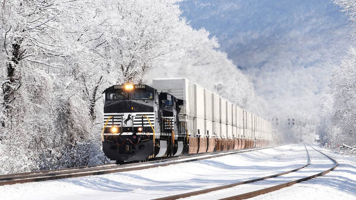 A photograph of a Norfolk Southern train traveling through a snowy landscape.