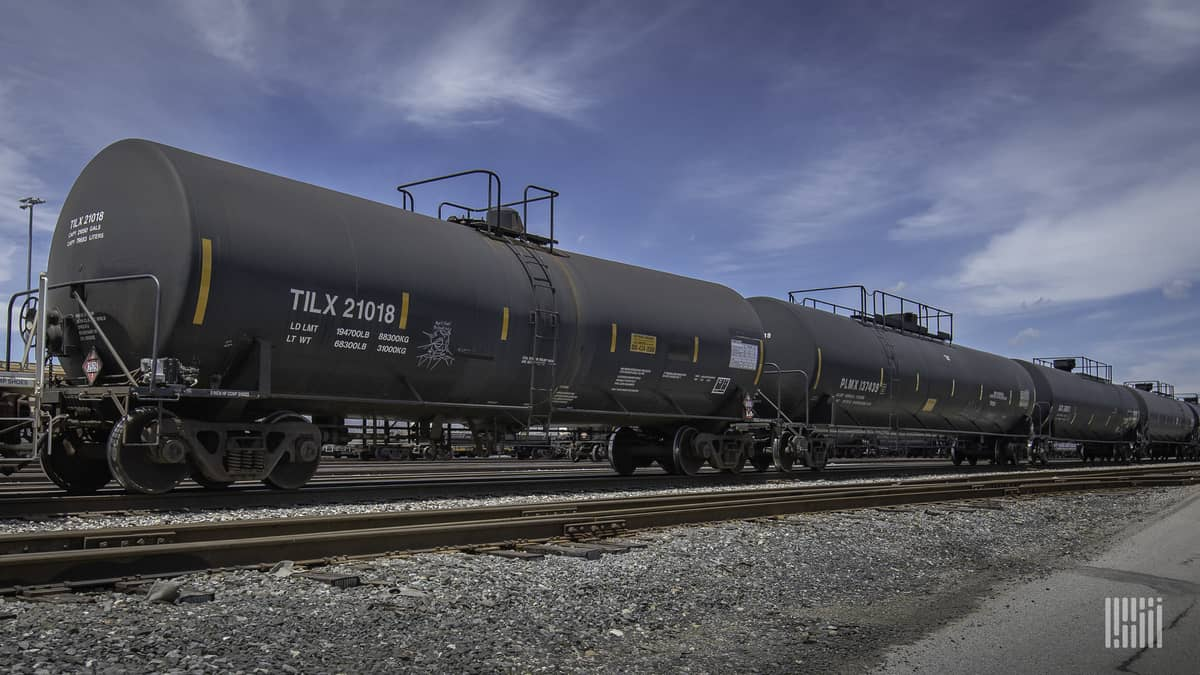 A photograph of a tank car parked in a rail yard.