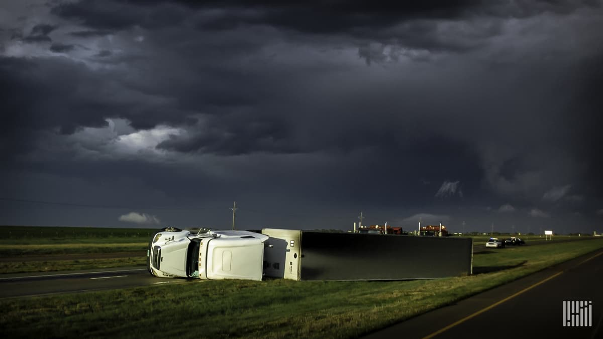 Tractor-trailer blown over along a highway.