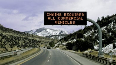 """Chains Required"" sign olong mountain highway."