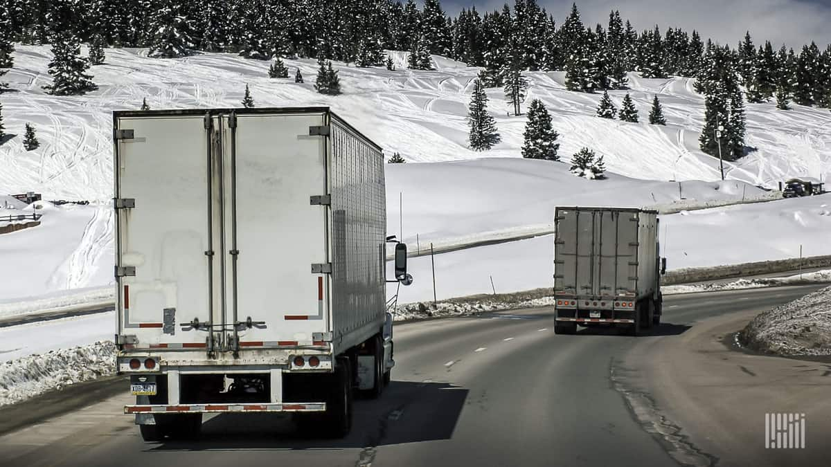 Tractor-trailers on a slick highway with snow in the surrounding mountains.