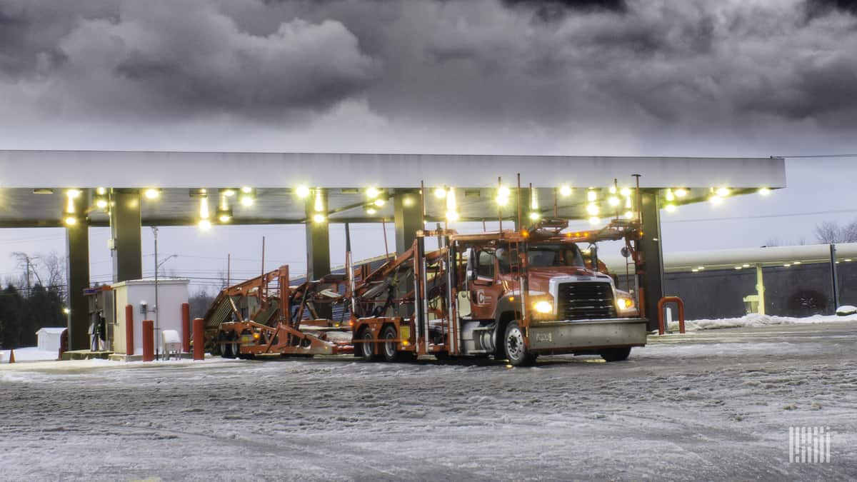 Tractor-trailer at a truck stop on a snowy day.
