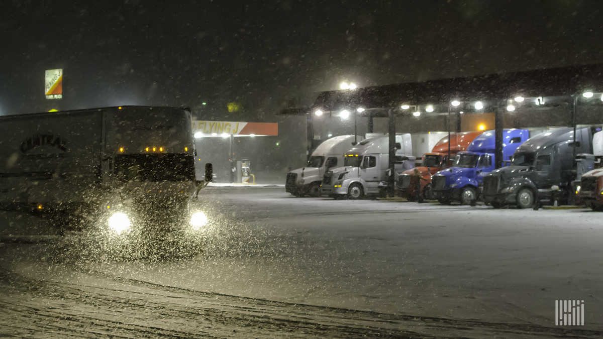 Tractor-trailers at a truck stop on a snowy night.