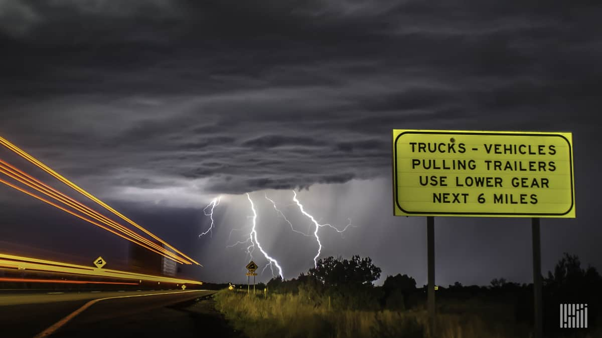 Tractor-trailers heading down a highway, with lightning across a dark sky.