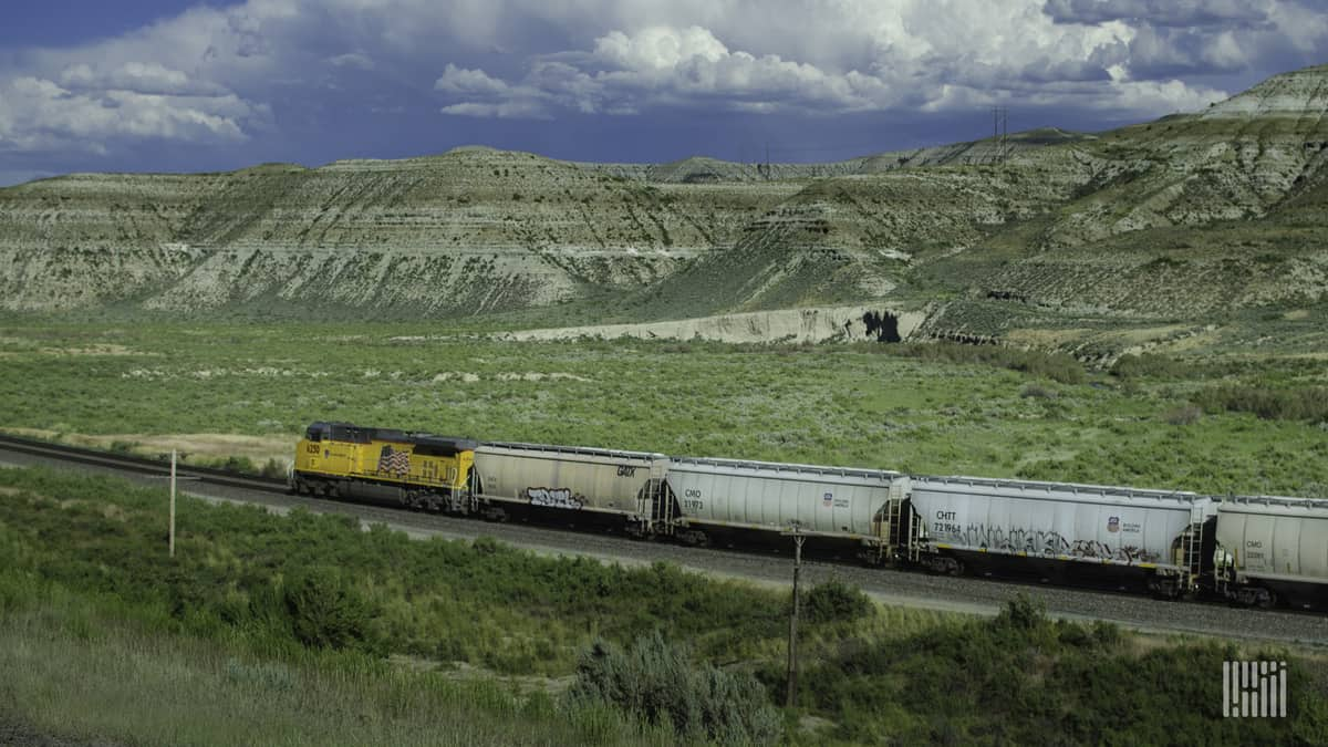 A photograph of a Union Pacific train traveling through a grassy field.