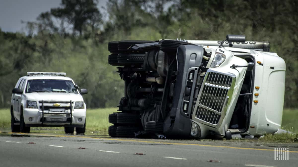 Flipped tractor-trailer on the side of a road.