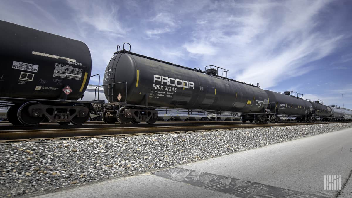 A photograph of three tank cars parked in a rail yard.