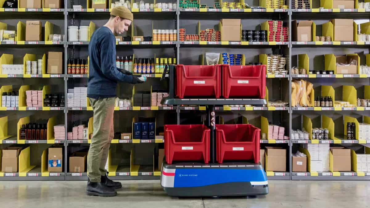A warehouse worker with a robot from 6 River Systems. The CEO of Shopify says warehouse automation will play a key role in scaling its fulfillment network.