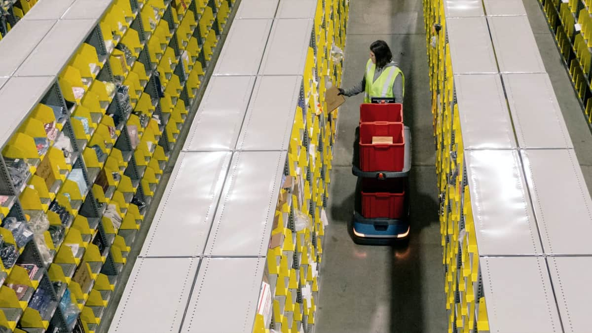 A robot helps a warehouse worker at a Shopify fulfillment facility.