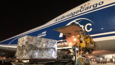 A 747 jumbo cargo plane gets loaded with large coolers containing pharmaceutical products.