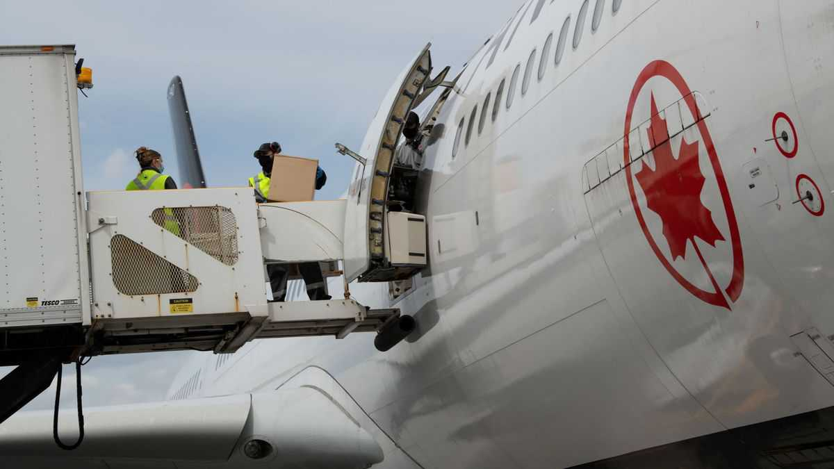 Cargo being loaded from hydraulic lift through side door of white Air Canada jet.