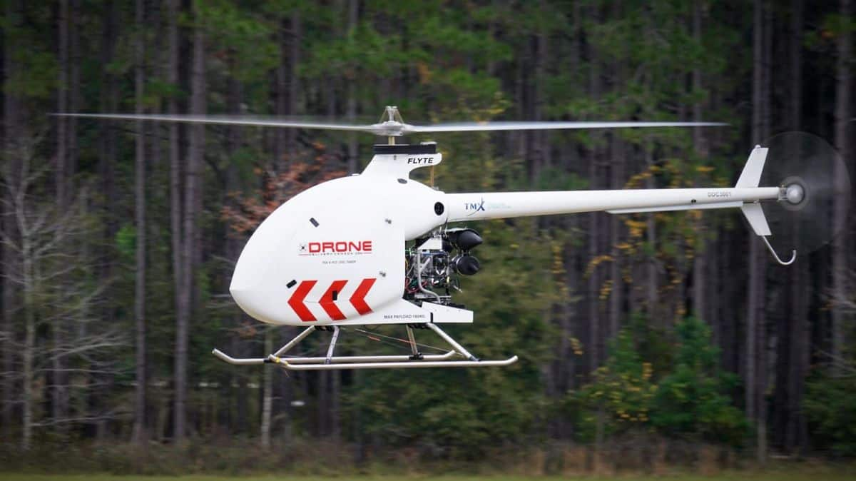 A white drone that looks like a helicopter flying with trees in background.