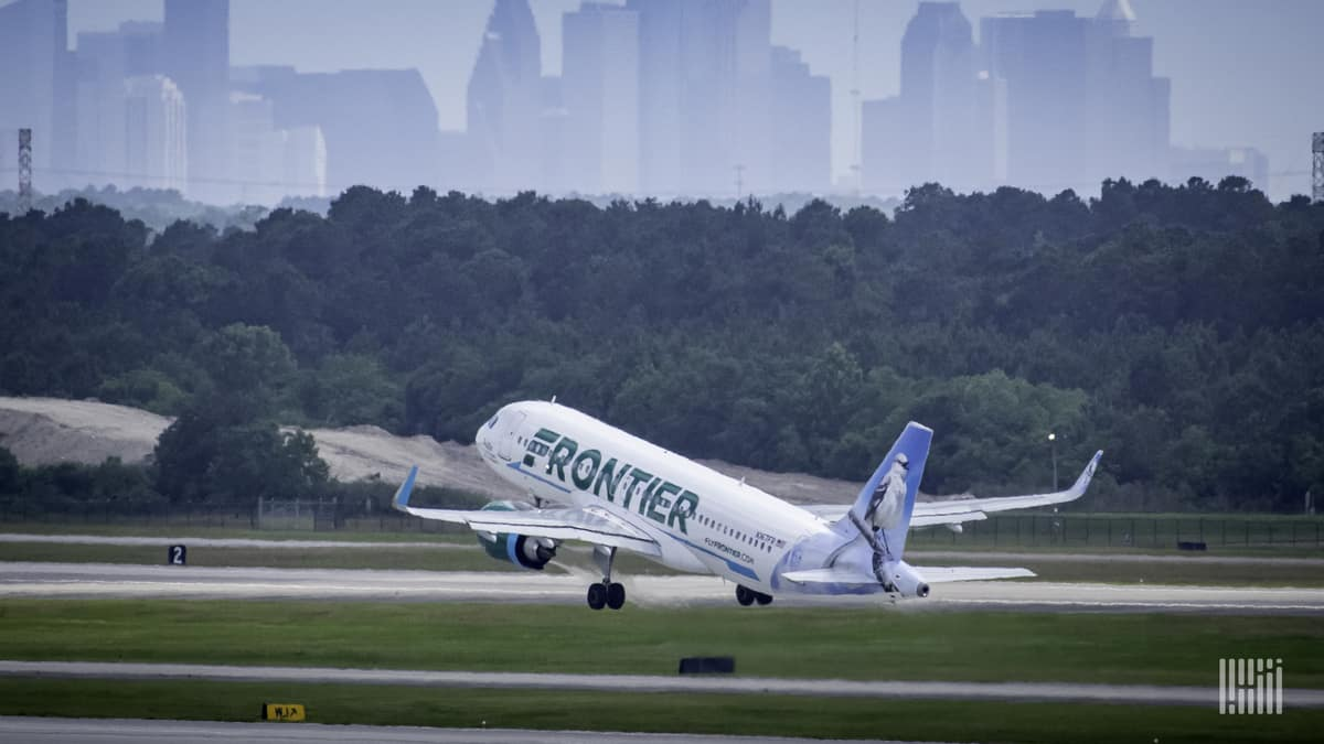 A white jet with light green tail lifts off runway with green trees and city skyline in the background.