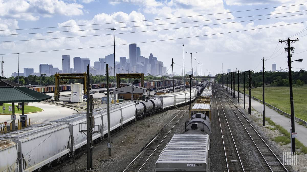 A photograph of a rail yard with city skyscrapers in the background.
