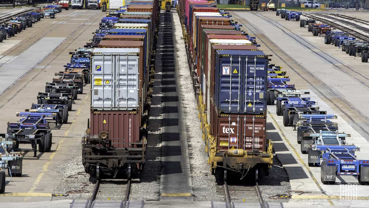 A photograph of intermodal containers and chassis parked in a rail yard.