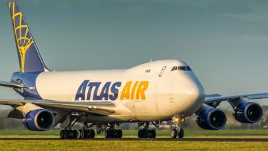 A white jumbo jet with Atlas Air name and blue tail painted on it. on sunny day rolls down airport roadway.