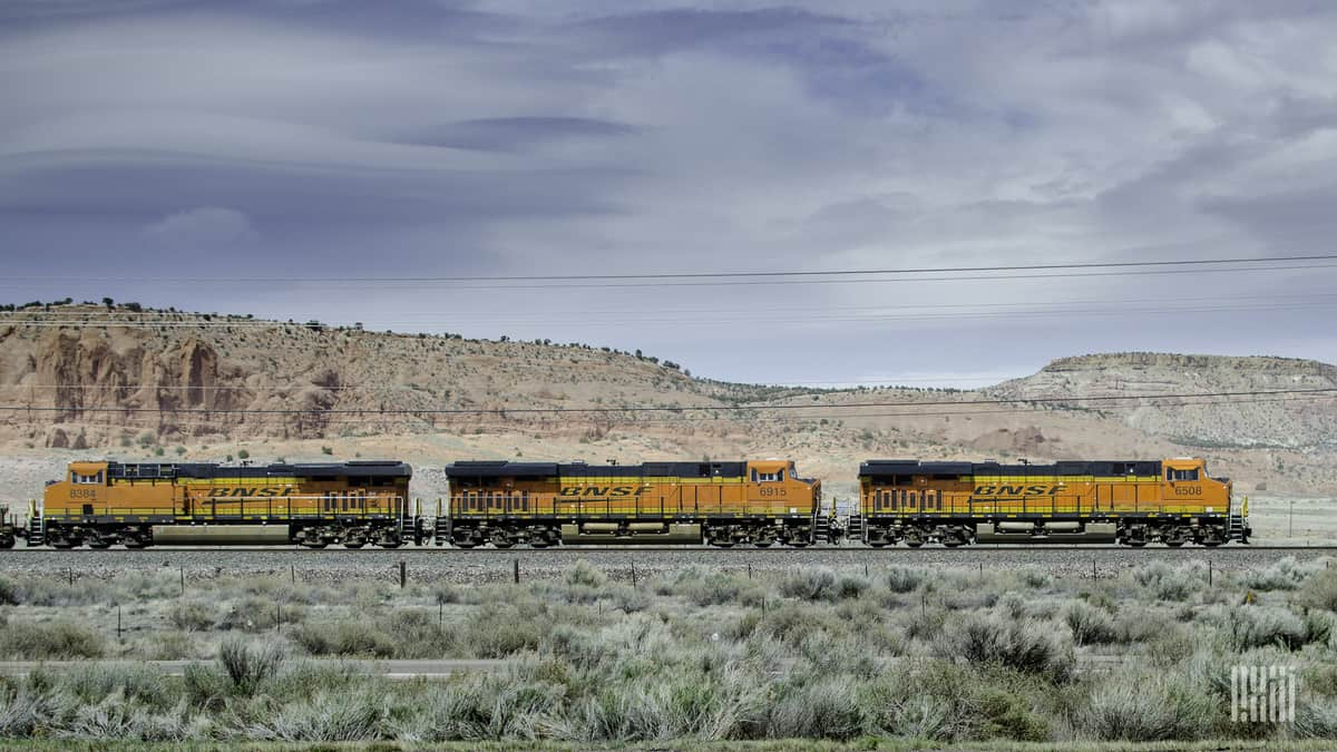 A photograph of a BNSF train passing by a desert mountain.