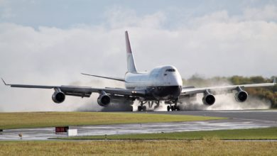 A British Airways 747 touching down on runway with smoke from tires.