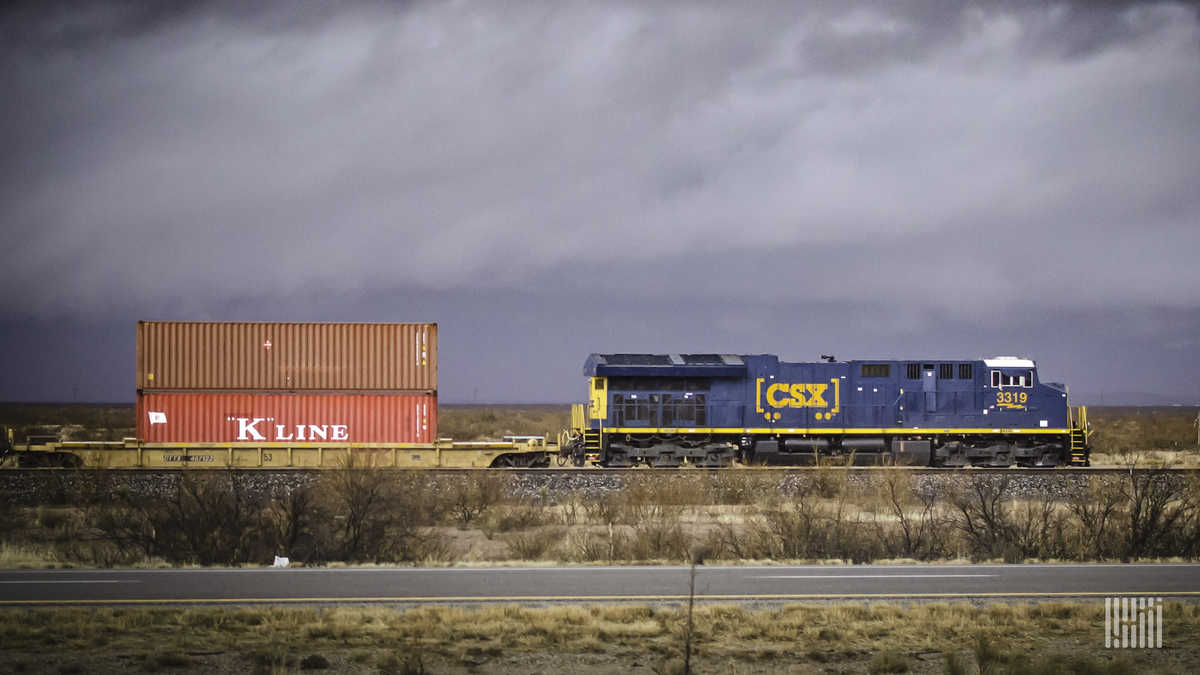 A photograph of a CSX train pulling intermodal containers across a field.