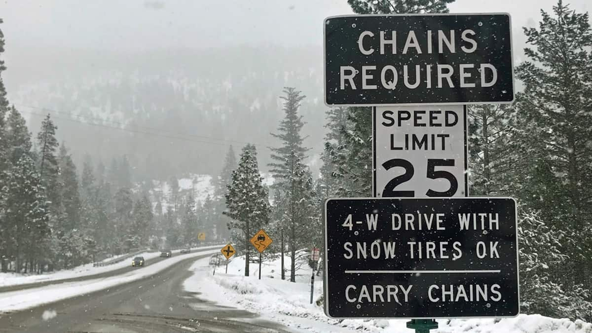 """""""Chains required"""" sign along a snowy California highway."""