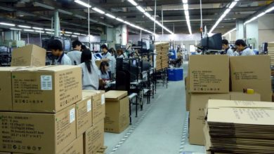Inside a small Chinese factory assembly line with boxes piled up.