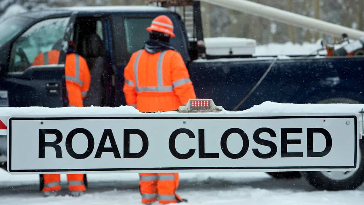 "Road crew standing in the snow next to ""Road Closed"" sign."