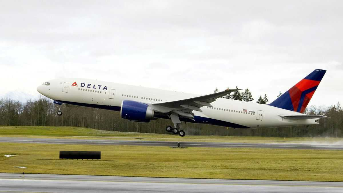A big white Delta jet with blue tail takes off from runway.