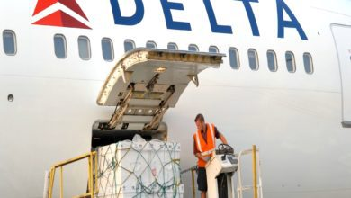A pallet of cargo on a hydraulic lift gets moved into the side door of a white Delta Air Lines airplane.