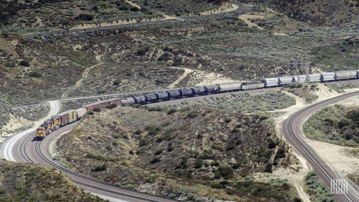A photograph of a train traveling across a barren mountain range.
