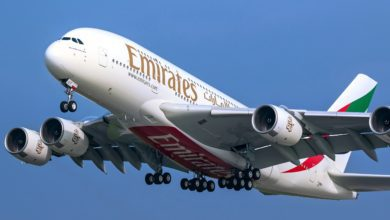A giant white Emirates plane with four engines and wheels down comes in for a landing behind a blue sky.