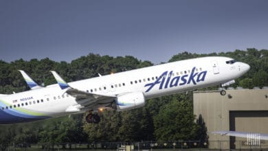 A white Alaska Airlines jet coming in for a landing with wheels down, about to touch down on runway on sunny day.