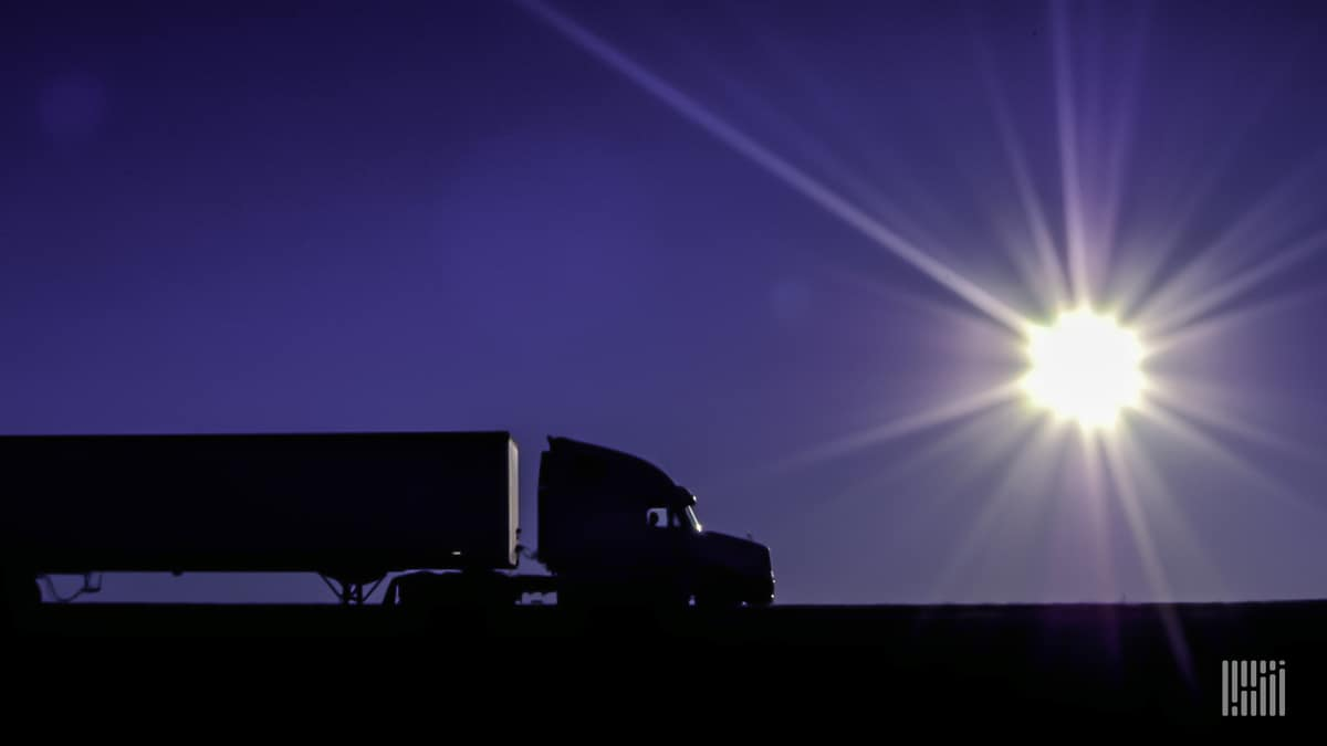 Tractor-trailer heading down a highway at dusk/dawn with bright sun on the horizon.