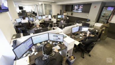 Brokers inside office sitting in front of computer screens