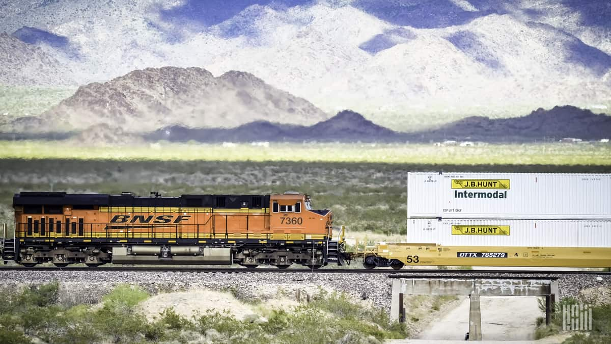 A passing flash identifies BNSF locomotive No. 7360 pulling an intermodal stack car with BNSF domestic containers across the Southwest desert. (Photo: Jim Allen/FreightWaves)