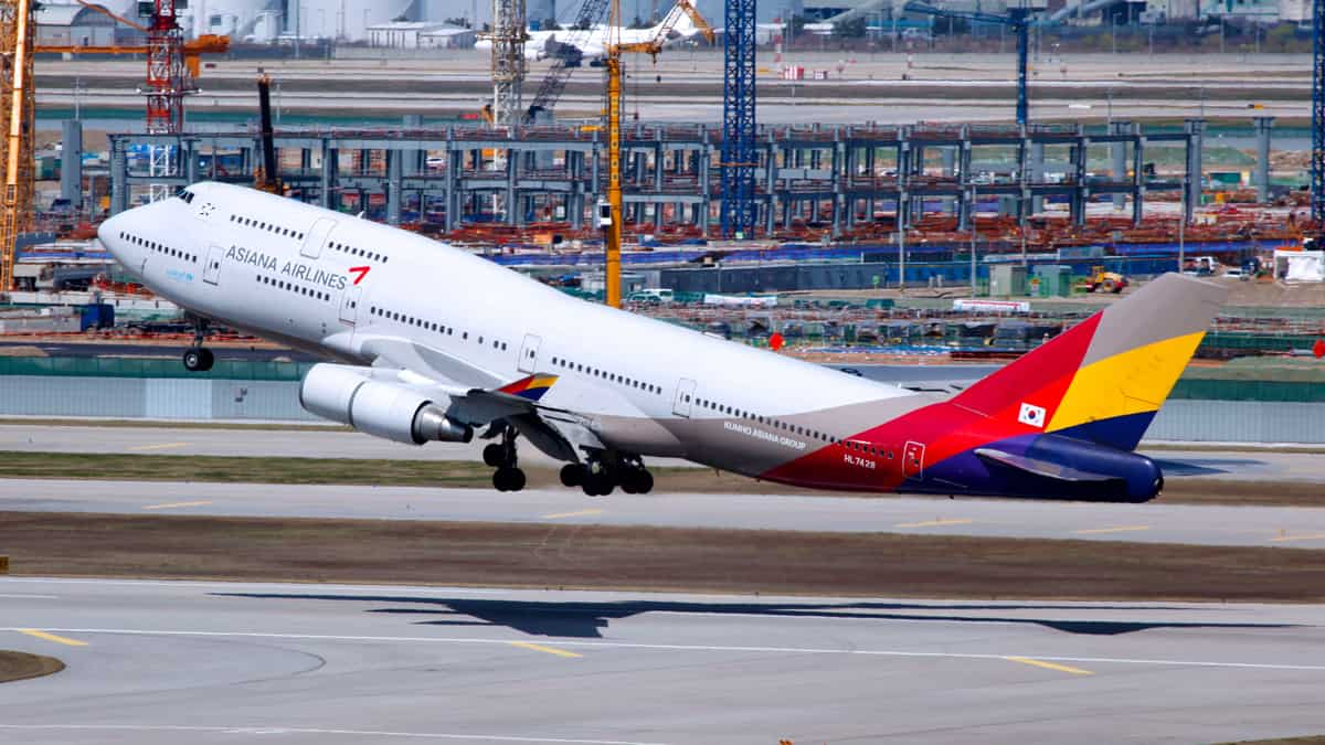 An Asiana jumbo jet with white fuselage and multicolored tail lifts off from runway.