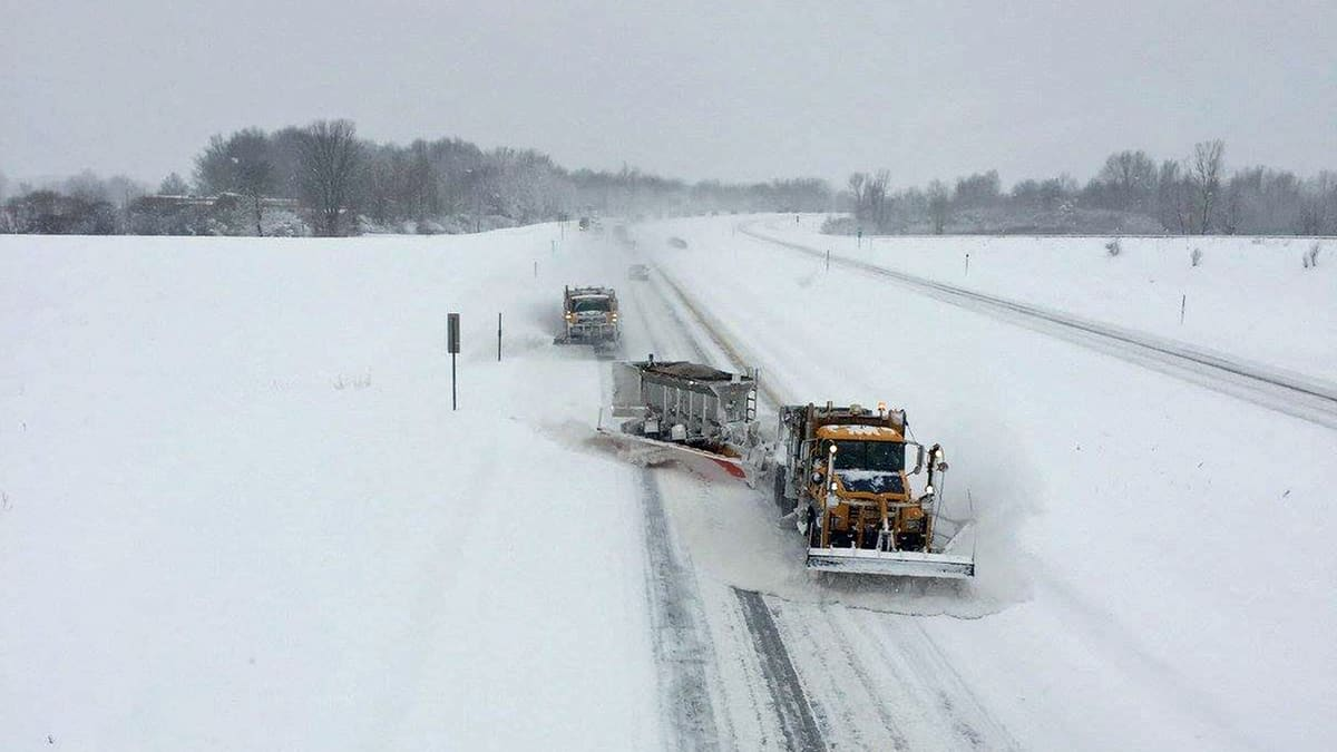 Several plow trucks on a snowy New York state highway.